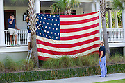 Homeowners hang a giant American flag on their home in the I'On neighborhood on Independence Day July 4, 2015 in Mt Pleasant, South Carolina.
