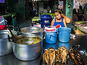 30 DECEMBER 2015 - BANGKOK, THAILAND:  A street food vendor sells fried fish and curries in Bang Chak Market. The market is supposed to close permanently on Dec 31, 2015. The Bang Chak Market serves the community around Sois 91-97 on Sukhumvit Road in the Bangkok suburbs. About half of the market has been torn down. Bangkok city authorities put up notices in late November that the market would be closed by January 1, 2016 and redevelopment would start shortly after that. Market vendors said condominiums are being built on the land.           PHOTO BY JACK KURTZ