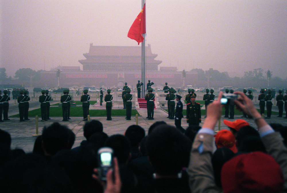 The lowering of the chinese flag in a vail of smog in front of the forbidden city. Seven of the ten most polluted cities in the world are located in China, due primarily to the country's dependence on coal for energy and dilapidated heavy industries..Beijing, China. 05/11/2005.Photo © J.B. Russell