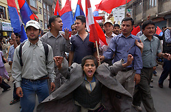 Children march past discarded posters of King Gyanendra and Queen Komal as thousands of people arrive to celebrate Democracy Day and to greet  the Queen who was marking her 55th birthday in Kathmandu, Nepal February 18, 2005.  Nepal marked its annual Democracy Day under emergency rule with severe press censorship, telephones cut and streets flooded with security forces.  King Gyanendra got rid of the government and declared emergency rule on February 1 saying that the country  is under threat from Maoist rebels and political instability.  The Maoist insurgency has claimed over 11,000 lives since 1996. (Ami Vitale)