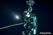 seventeen year old Zoe Molder, tethered to a dive boat drifting in the open ocean, uses her dive light to illuminate a gelatinous invertebrate on a blackwater dive in the surface waters of the deep  ocean at night, Kona, Hawaii, USA ( Central Pacific Ocean ) MR 480