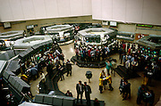 An aerial view of the 1980s options trading floor at the London Stock Exchange. We look down from a high vantagepoint on to the traders as they go about their business. Three years after the so-called Big Bang in 1986 , this location at the old Stock Exchange Tower  became redundant with the advent of the Big Bang, which deregulated many of the Stock Exchange's activities as it enabled an increased use of computerised systems that allowed dealing rooms to take precedence over face to face trading. Thus, in 2004, the House moved to a brand new headquarters in Paternoster Square, close to St Paul's Cathedral.