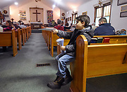 10-year-old Oscar Anderson hands out the day's readings to parishioners as they make their way into Spirit of Faith church on Sunday for service in Woonsocket. (Matt Gade / Republic)