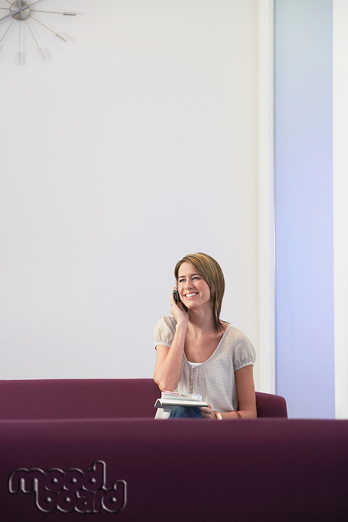 Smiling casually dressed Businesswoman sitting on sofa Using mobile