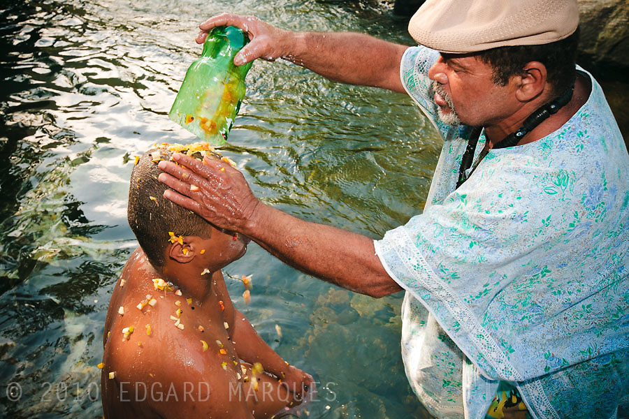 "CANDOMBLE SUFFERED PERSECUTIONS SINCE ITS BIRTH IN BRASIL. NOW, UNDER THE PRESSURE OF GROWING EVANGELISM, IT'S TIME TO LOOK FOR ACEPTANCE. FATHER JURANDIR AND HIS ""FILHOS DE SANTO"" TRAVEL MAS DE 50 KM TO A RITUAL AT A WATERFALL. THIS RITUAL IS PART OF THIS 'SON OF SAINT"" OBLIGATIONS. / EL CANDOMBLE SUFRIO PERSECUCIONES DESDE SU NACIMIENTO EN BRASIL. AHORA, SO PRESION DEL EVANGELISMO CRECIENTE, BUSCA LA ACEPTACION PARA SOBREVIVIR. PADRE JURANDIR Y SUS ""HIJOS DE SANTO"" VIAJAN MAS DE 50 KM PARA REALIZAR UN RITUAL EN UNA CASCADA. EL RITUAL ES PARTE DE LAS ""OBLIGACIONES"" DEL HIJO DE SANTO."