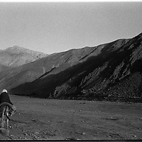 A young boy leads a donkey carrying a younger sibling along the Panshir valley road, Afghanistan. (Greg Marinovich)