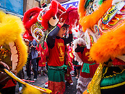"""19 FEBRUARY 2015 - BANGKOK, THAILAND: Lion dancers take a break on Chinese New Year on Yaowarat Road in Bangkok. 2015 is the Year of Goat in the Chinese zodiac. The Goat is the eighth sign in Chinese astrology and """"8"""" is considered to be a lucky number. It symbolizes wisdom, fortune and prosperity. Ethnic Chinese make up nearly 15% of the Thai population. Chinese New Year (also called Tet or Lunar New Year) is widely celebrated in Thailand, especially in urban areas that have large Chinese populations.    PHOTO BY JACK KURTZ"""