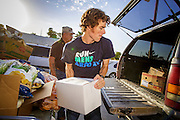 07 AUGUST 2012 - TOLLESON, AZ: NEIL MCDONAGH, a volunteer at the food bank in Tolleson, AZ, loads food into a waiting truck Tuesday. The Tolleson food bank has been operating for more than 20 years. It used to serve mostly the families of migrant farm workers that worked the fields around Tolleson but in the early 2000's many of the farms were sold to real estate developers. Now the food bank serves both farm worker families and people who lost their homes in the real estate crash, that his Phoenix suburbs especially hard. More than 150 families a day are helped by the Tolleson food bank, an increase of more than 50% in the last five years.   PHOTO BY JACK KURTZ