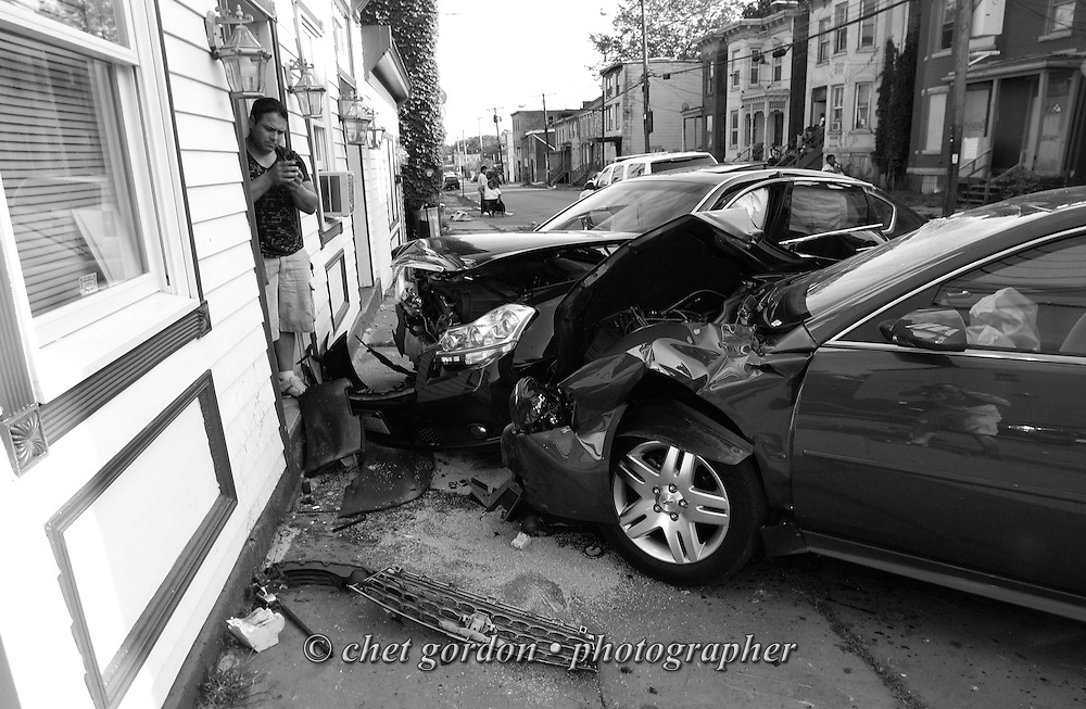 NEWBURGH, NY.  A man uses a smartphone to photograph the scene of a two car motor vehicle accident at the intersection of Lander St. and First Ave. in Newburgh, NY on Sunday, July 17, 2011.  © www.chetgordon.com/blog