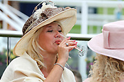 A racegoer enjoying a glass of champagne at the York Dante Meeting at York Racecourse, York, United Kingdom on 16 May 2018. Picture by Mick Atkins.