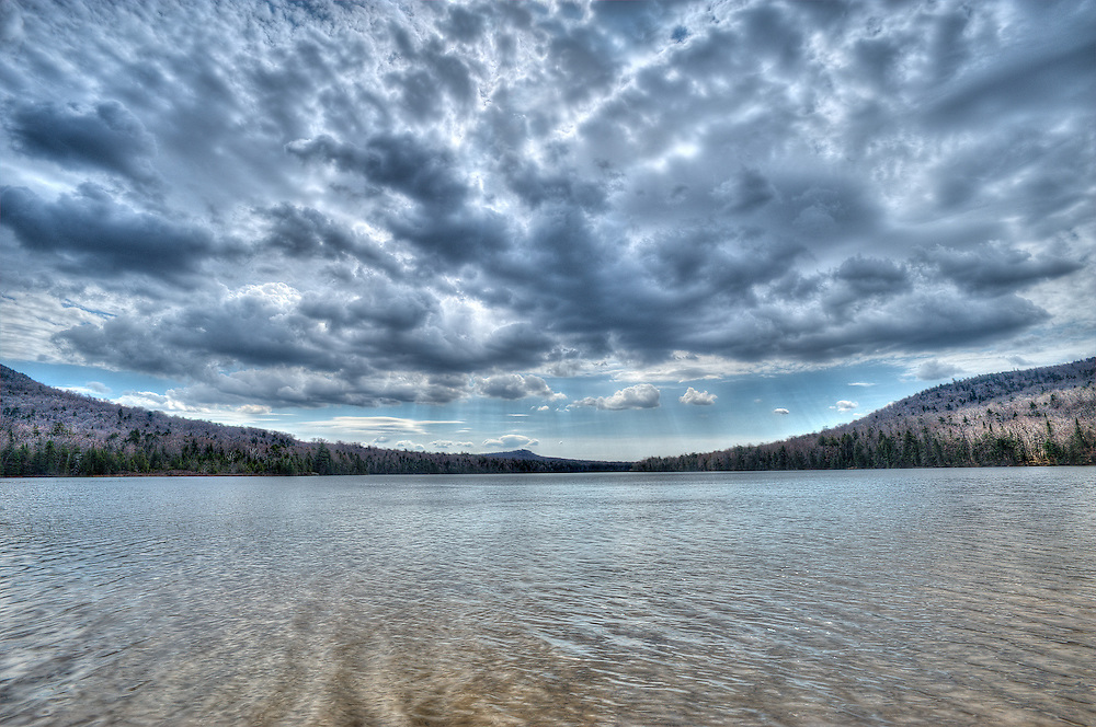 Tirrell Pond, Adirondacks, NY.<br /> As so often happens up here, what began as a beautiful spring morning broke down at the destination.  Today's was Tirrell Pond, really more of a lake, sitting beneath Blue Mountain...a fitting destination itself for my mood.  Whike I walked the shores a bit,  the heavy skies seemed to stall overhead, dark clouds piling up above me as the breeze faltered for awhile.  I sat and thought of nothing, meaning of course everything, for awhile, basking in warmth when sun spots found their way to my end of the lake.  I pulled my rain gear, and set up the photo gear, suppressing my dark down side in the act of tending to the task at hand.  Or perhaps it was the storm, gathering as it was, that pulled negativity into it's clutch.  Finished, I gathered my pack and other baggage as well, and hiked back to my car.  It never did rain.