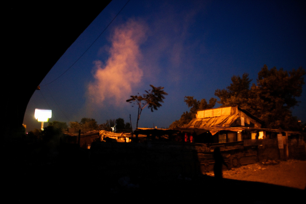 Smoke floats over the Nova Gazela settlement from a garbage fire.