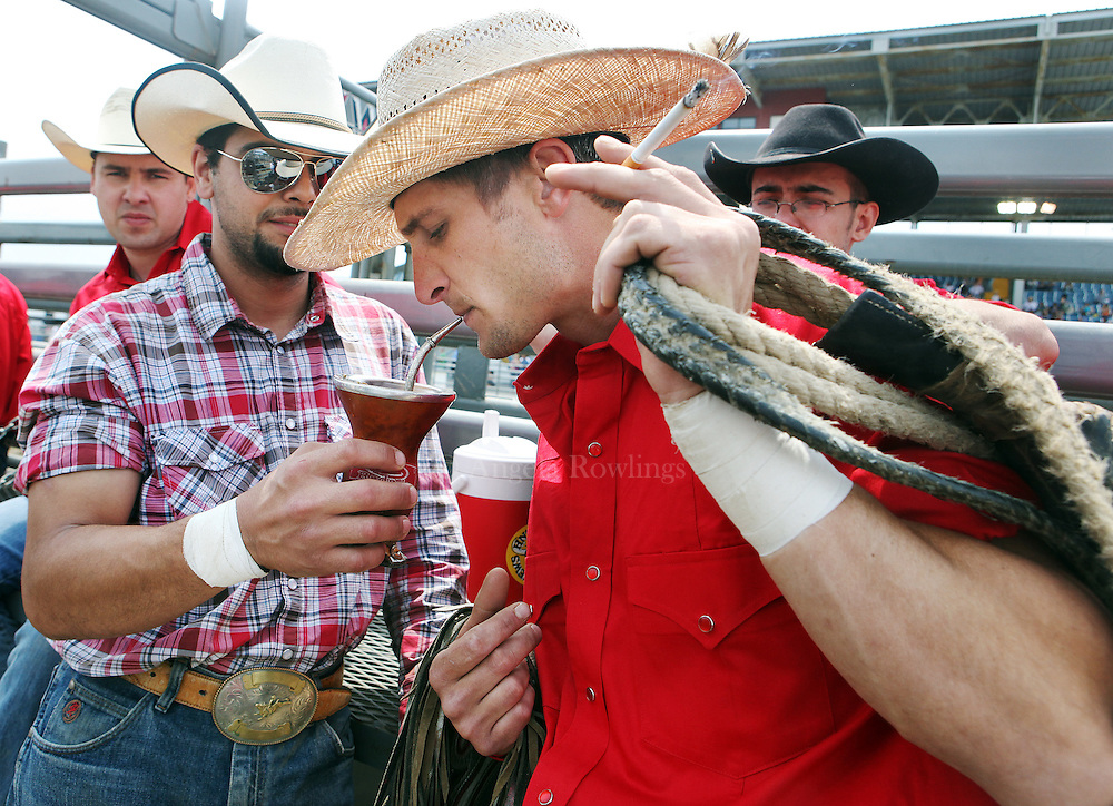 Rafael Melotti, 26, of Dedham, left, offers Justin Shue, of Lancaster, Penn., a taste of his terere mate prior to competing in the Barretos na America rodeo at the Brockton Fairgrounds, Sunday, May 24, 2009.  Terere mate is an infusion of yerba mate prepared with cold water like an iced tea, and then passed around as a social ritual.