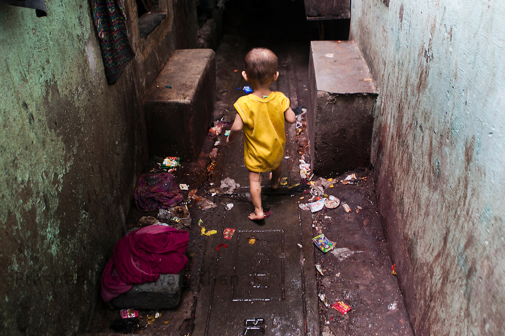 Dharavi,Mumbai, Maharashtra, India, 24 July 2012:.A child wanders alone in the dark bylanes of Dharavi outside  a cramped up Anganwadi center in the metropolis of Mumbai. To combat undernutrition in young children, the Government of India relies largely on the Integrated Child Development Scheme (ICDS). Begun in 1975, the scheme provides health and nutrition education for mothers of infants and young children, along with other services, such as supplementary nutrition, basic health and antenatal care, growth monitoring and promotion, preschool non-formal education, micronutrient supplementation and immunization. UNICEF is collaborating with the Government of India to increase the effectiveness of ICDS. UNICEF India/2012/Vishwanathan