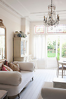 Daybed with cushions and glass chandelier in white home interior