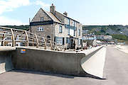 Wave return wall, The Cove House Inn historic building at Chiswell, Isle of Portland, Dorset, England, UK