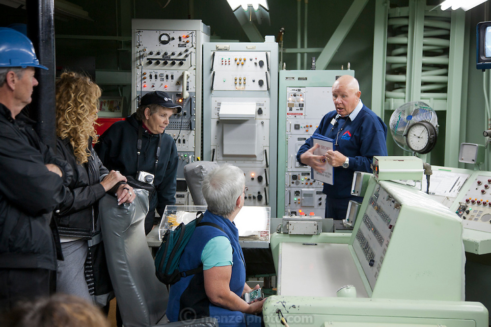 Control room with tourists at the Titan Missile Museum, Green Valley, Arizona. When the SALT Treaty called for the de-activation of the 18 Titan missile silos that ring Tucson, volunteers at the Pima Air Museum asked if one could be retained for public tours. After much negotiation, including additional talks with SALT officials, the Green Valley complex of the 390th Strategic Missile Wing was opened to the public. Deep in the ground, behind a couple of 6,000 pound blast doors is the silo itself. The 110 foot tall missile weighed 170 tons when it was fueled and ready to fly.