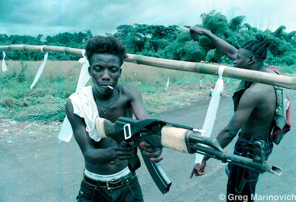 IPMG0895 Bo Waterfront, Liberia. A group of LURD rebels loyal to Sekouh Conneh Jr fool around at a roadblock between Monrovia and the border crossing with Sierra Leone at Bo Waterfront, Sept 22, 2003. Liberia's decades long civil conflict has destabilised the entire region and turned a generation of youth into fighters.  Greg Marinovich/South Photographs