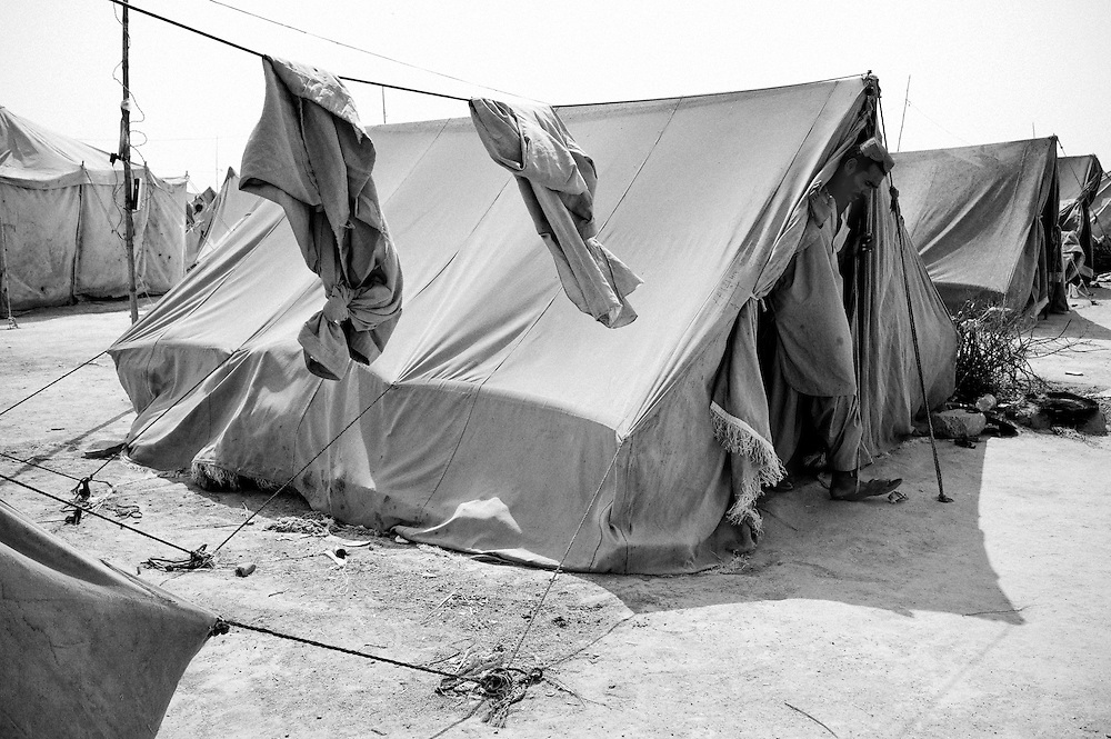 Mohammad Ali leaves the tent to help out one of the neighboors. Karachi, Pakistan, 2010