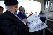 May 10, 2013 - New York, NY. Lazar Tarler glancing over the project folder he took on the tourist ferry ride for a formal portrait photo shoot. 04/20/2013 Photograph by Natalia V. Osipova/CUNY Journalism PHOTO