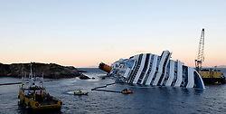 An oil recovery sea platform (R) is seen next to the Costa Concordia cruise ship off the west coast of Italy, at Giglio island January 25, 2012. The captain of the Italian liner Costa Concordia said he was told by managers to take his ship close to shore on the night it ran aground and capsized, but the company denied having any prior knowledge of the manoeuvre.<br /> REUTERS/Darrin Zammit Lupi (ITALY)
