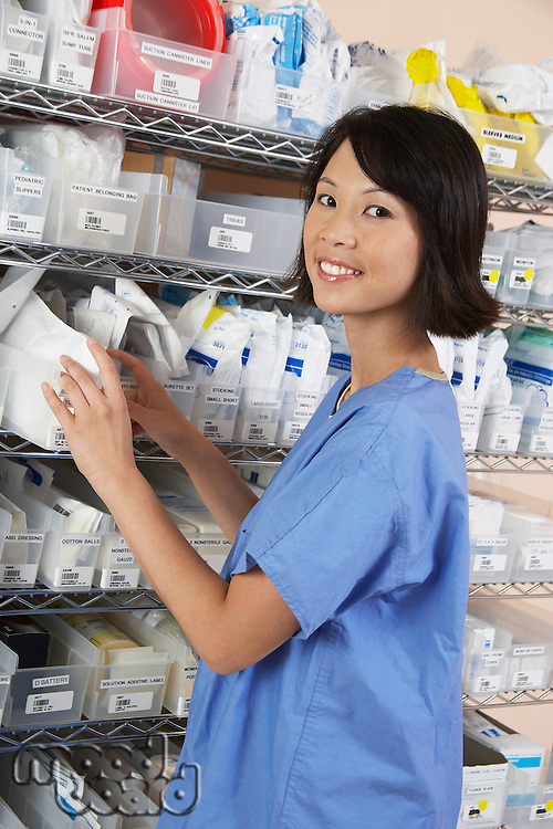 Female nurse standing at shelf with medicines, portrait