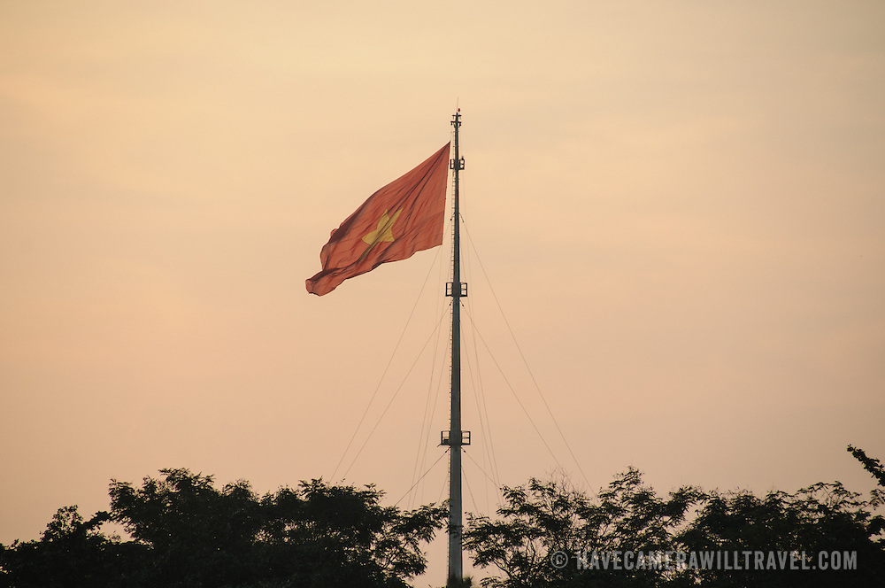 The Vietnamese flag in the haze, flying on top of the citadel at the Imperial City in Hue, Vietnam. A self-enclosed and fortified palace, the complex includes the Purple Forbidden City, which was the inner sanctum of the imperial household, as well as temples, courtyards, gardens, and other buildings. Much of the Imperial City was damaged or destroyed during the Vietnam War. It is now designated as a UNESCO World Heritage site.