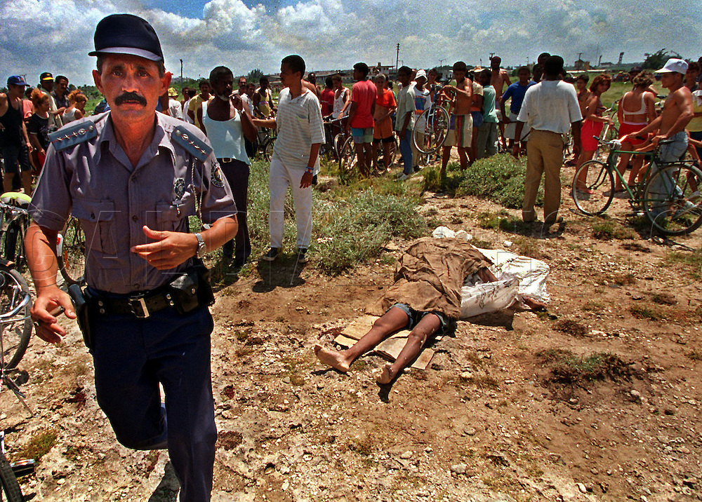 8/21/1994-Al Diaz/Miami Herald--In 1994 Cuban balseros turned the tiny fishing village of Cojimar into a major point of embarkation for thousands seeking a better life. Here, A Cuban policeman disperses a crowd of onlookers viewing the corpse of a Cuban rafter washed ashore and dragged to this location at Cojimar.