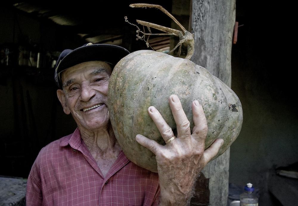 A farmer holds up his prize pumpkin near Paraty, Sao Paulo State, Brazil