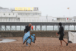 © Licensed to London News Pictures. 26/07/2015. Brighton, UK. Staff from a Brighton beach deckchair company bring chairs to the beach as rain and high winds is hitting Brighton and the South Coast. Today July 26th 2015. Photo credit : Hugo Michiels/LNP