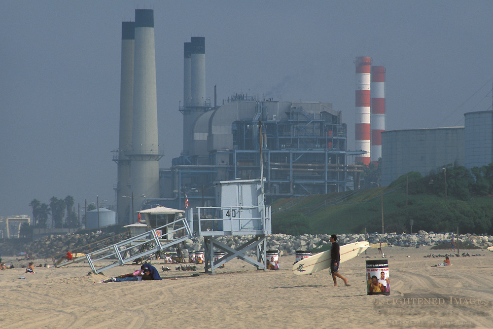 Surfer walking across sand below industrial power plant and smokestack, Manhattan Beach, Los Angeles County, California