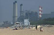 Surfer walking across sand below industrial power plant and smokestack, Manhattan Beach, Los Angeles County, California