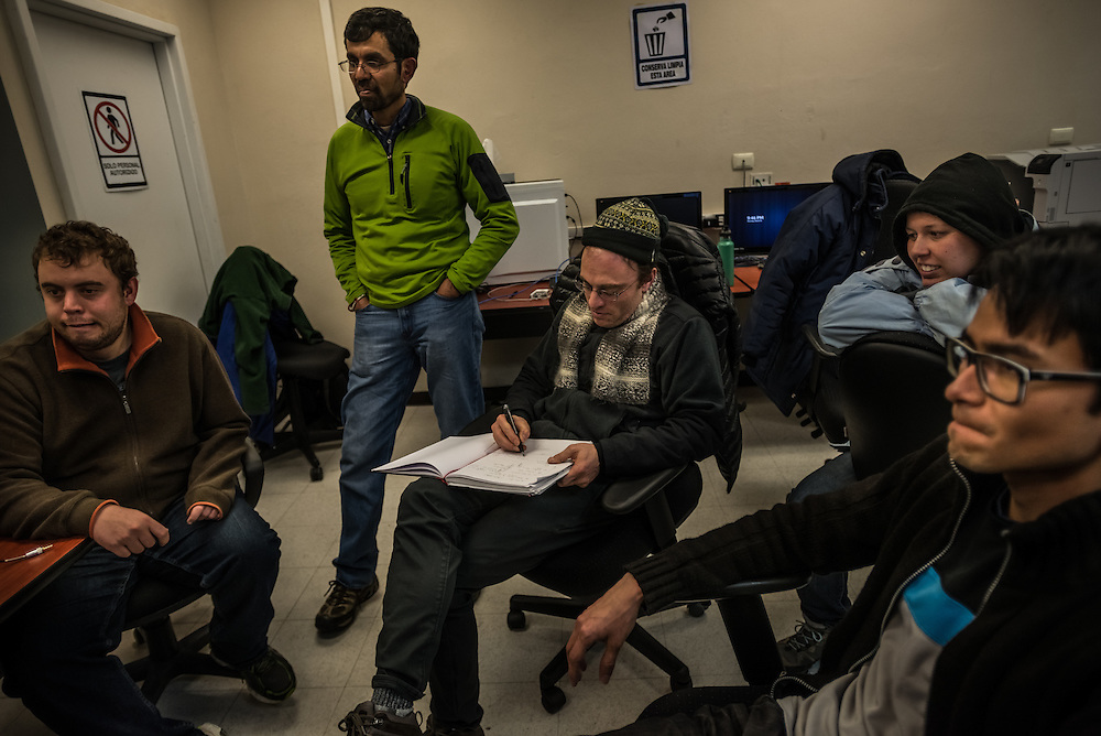 PICO DE ORIZABA NATIONAL PARK, PUEBLA, MEXICO - MARCH 27, 2015: Astronomer Sheperd Doeleman of MIT, (center) makes notes in his notebook surrounded by his team, while monitoring the data being received inside the control room of the Large Millimeter Telescope after successfully connecting the LMT to several other telescopes around the world to make one large telescope called the Event Horizon Telescope, as large as the earth that the LMT team believes has the capacity to make the first image of the black hole.   CREDIT: Meridith Kohut for The New York Times
