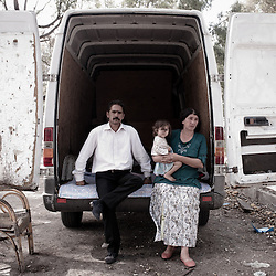 Rome, Italy - 27 September 2012: a Bosnian family poses for a picture in front of the caravan where they live. After the eviction, the local authorities have offered to resettle the families in a temporary emergency structure and eventually in two authorized camps, Castel Romano and La Barbuta. The two authorized camps are destined only for Roma and are located in remote areas in the suburbs with little access to the basic services of the community.