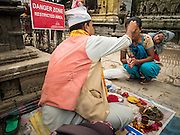 31 JULY 2015 - KATHMANDU, NEPAL: A Hindu holy man blesses a woman and her child in front of sign warning of dangers from the earthquake at Swayambhunath, also known as the Monkey Temple. It's a complex of Buddhist and Hindu temples in Kathmandu. It was heavily damaged in the Nepal Earthquake. The Nepal Earthquake on April 25, 2015, (also known as the Gorkha earthquake) killed more than 9,000 people and injured more than 23,000. It had a magnitude of 7.8. The epicenter was east of the district of Lamjung, and its hypocenter was at a depth of approximately 15 km (9.3 mi). It was the worst natural disaster to strike Nepal since the 1934 Nepal–Bihar earthquake. The earthquake triggered an avalanche on Mount Everest, killing at least 19. The earthquake also set off an avalanche in the Langtang valley, where 250 people were reported missing. Hundreds of thousands of people were made homeless with entire villages flattened across many districts of the country. Centuries-old buildings were destroyed at UNESCO World Heritage sites in the Kathmandu Valley, including some at the Kathmandu Durbar Square, the Patan Durbar Squar, the Bhaktapur Durbar Square, the Changu Narayan Temple and the Swayambhunath Stupa. Geophysicists and other experts had warned for decades that Nepal was vulnerable to a deadly earthquake, particularly because of its geology, urbanization, and architecture.        PHOTO BY JACK KURTZ