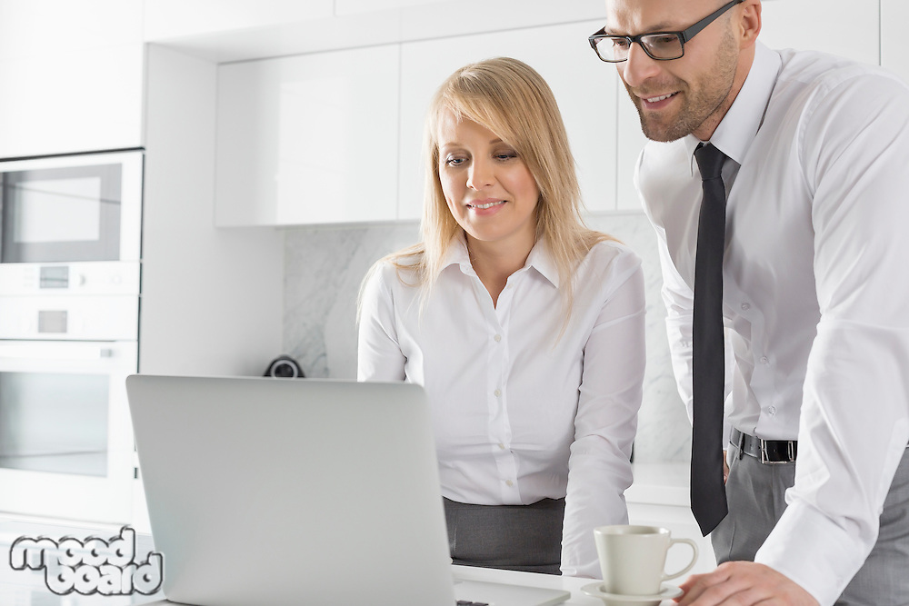 Happy mid adult business couple using laptop at kitchen counter
