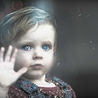 A young girl with bright blue eyes looking out of a window