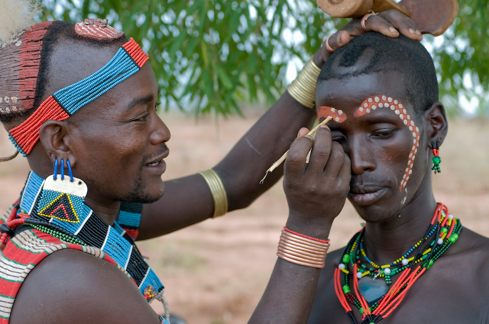 Man is painting one´s face for the jumping of the bull ceremony,Ethiopia,Africa