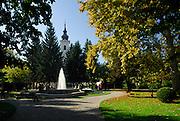 Fountain and Strossmayer Promenade (Strossmayerova setalista), town square park, with new Church of Saint Lawrence (Crkva Sveti Lovre) in background. Petrinja, Croatia