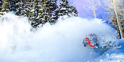Tim Hoff explodes across the forest on his Skidoo X. A trail of Powder billowing in his wake.