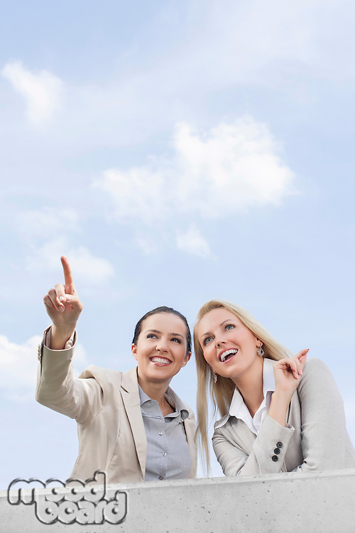 Low angle view of happy young businesswoman showing something to coworker while standing on terrace against sky