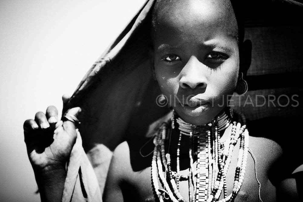 Young Arbore girl, in traditional outfit. These young girls are so beautiful. They wear many necklaces in bright colours and lovely earrings.This is a very exotic and a small tribe living in the Weyto Valley Desert living in a very harsh physical enviroment. The Arbore women generally wear a large black cloth to cover their heads. They perform many ritual-like dances while singing. They believe that dancing and singing with eliminate negative energies and give positive energy that will bring good-luck. The Arbore measure their wealth by the number of cattle they own..<br /> <br /> This is a very exotic and a small tribe living in the Weyto Valley Desert living in a very harsh physical enviroment. The Arbore women generally wear a large black cloth to cover their heads. They perform many ritual-like dances while singing. They believe that dancing and singing with eliminate negative energies and give positive energy that will bring good-luck. The Arbore measure their wealth by the number of cattle they own..