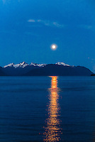 A full moon rising over the waters of the Inside Passage, southeast Alaska USA.