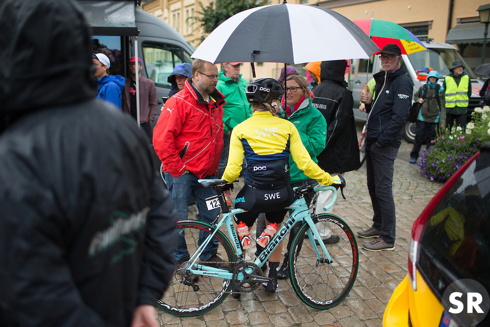Sara Olsson (SWE) of Team Sweden seeks refuge under an umbrella before the start of the 76,1 km first stage of the 2016 Ladies' Tour of Norway women's road cycling race on August 12, 2016 between Halden and Fredrikstad, Norway. (Photo by Balint Hamvas/Velofocus)