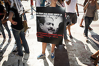 """TUNIS, TUNISIA - 26 JULY 2013: An anti-government activist holds a picture of the assassinated opposition leader Mohamed Brahmi saying """"He didn't die under the regime of Ben Ali…He was assasinated under the """"democracy"""" of the troika), by the National Constituent Assemby (NCA) in Tunis, Tunisia, on July 26th 2013.<br /> <br /> Tunisia, birthplace of the Arab Spring revolutionary movement, was plunged into a new political crisis on Thursday when assassins shot Mohamed Brahmi, 58, leader of the Arab nationalist People's Party, an opposition party leader outside his home in a hail of gunfire."""