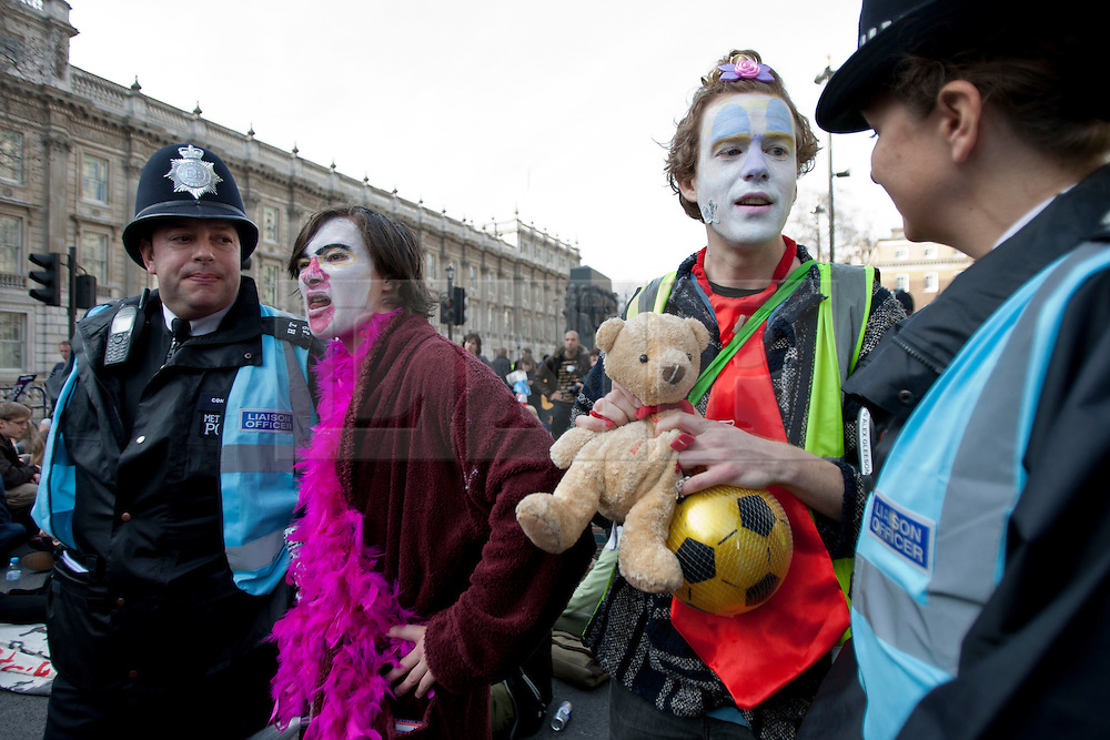 © licensed to London News Pictures. London, UK 14/03/2012. Two protesters are talking to police officers at the student demonstration against tuition fees and education cuts today in central London. Photo credit: Tolga Akmen/LNP