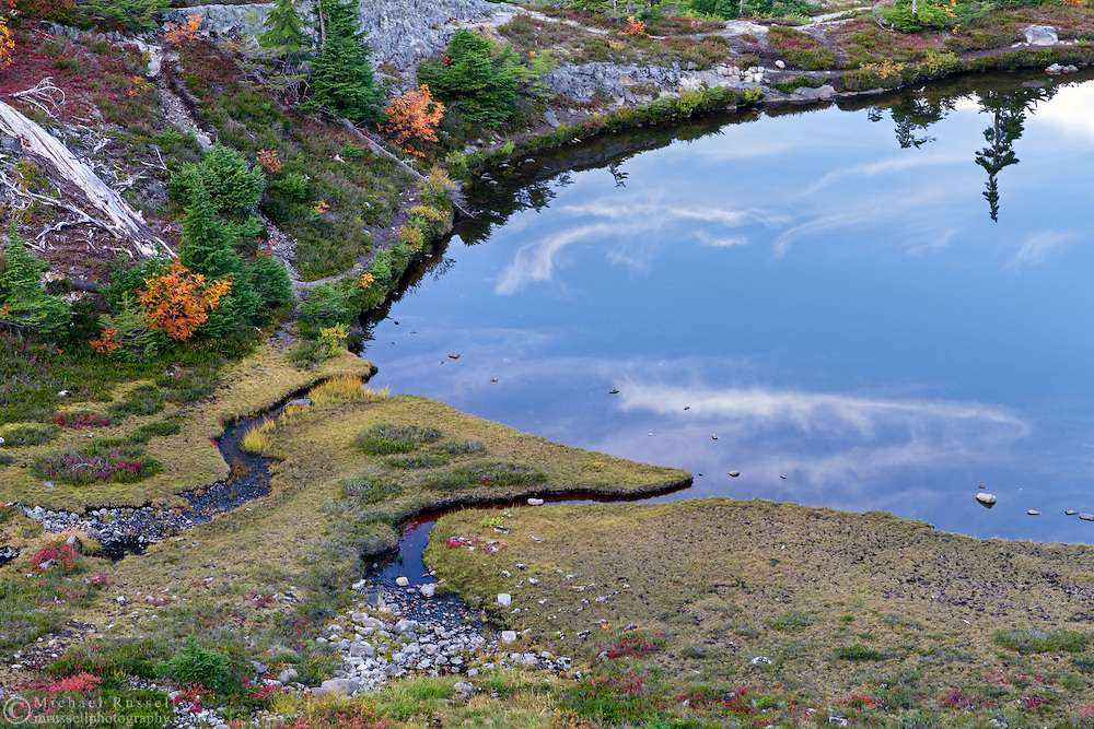 Clouds are reflected in Austin Pass Lake at the Heather Meadows area of the Mount Baker-Snoqualmie National Forest of Washington State, USA.