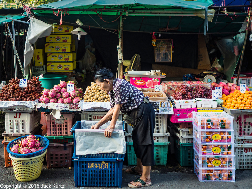 01 DECEMBER 2016 0 BANGKOK, THAILAND: A fruit vendor in the traditional market on Lan Luang Road in Bangkok. The market is on the site of one of the first western style cinemas in Bangkok. The movie theatre closed years ago and is still empty but the market fills the streets around the theatre.     PHOTO BY JACK KURTZ
