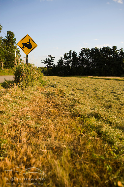 A tractor crossing sign next to a farm in Pepperell, Massachusetts.