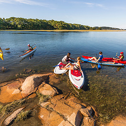 A group of kayakers and paddleboarders on the Essex River at the Cox Reservation in Essex, Massachusetts.